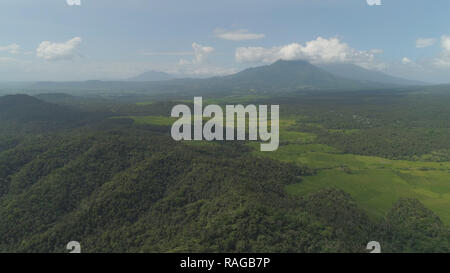 Aerial view of mountain valley with hills covered forest, trees, mount Iriga. Luzon, Philippines. Slopes of mountains with evergreen vegetation. Mountainous tropical landscape. - Stock Photo