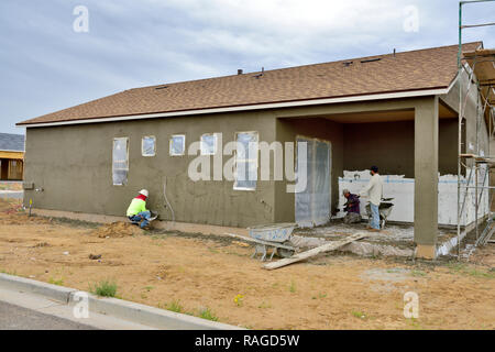 New timber frame house under construction with stucco being applied over insulation boards - Stock Photo