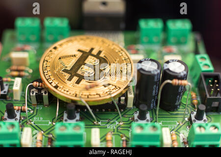 Bitcoin gold coin on computer circuit board microchips. Electronic cryptocurrency. - Stock Photo