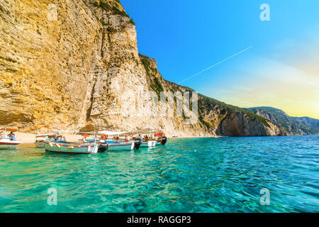 Boats line up at the shoreline in the clear waters off the sandy Paradise Beach or Chomi Beach on a sunny day in Corfu Greece. - Stock Photo