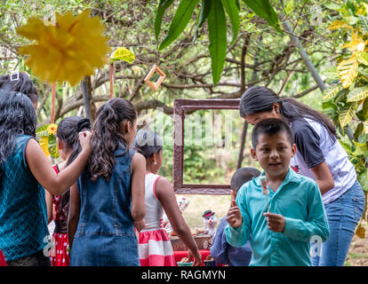 group of latin children looking at something at party in Guatemala - Stock Photo