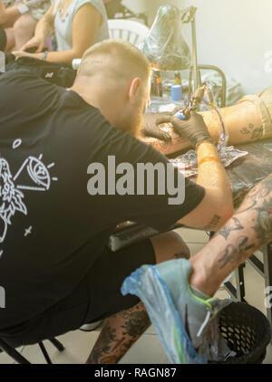 Tattoo artist makes a tattoo on a man's hand. - Stock Photo