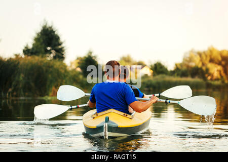 Young men rowing kayak on river at sunset. Couple of friends having fun canoeing in summer - Stock Photo