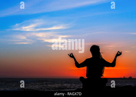 silhouette of a woman meditating in lotus pose with chakra