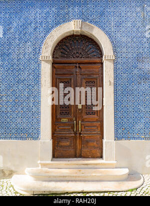 Lisbon - Portugal, facade of a house covered with typical blue tiles, azulejos, and ancient decorated wooden door - Stock Photo