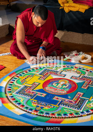 Traveling Tibetan Tashi Kyil Buddhist monks construct a blessed sand Chinrezig Mandala; ceremoniously to be dissolved in the Arkansas River; Salida; C - Stock Photo