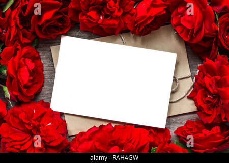 valentines day background. blank greeting card in frame made of red roses flowers. mock up. flat lay. top view - Stock Photo
