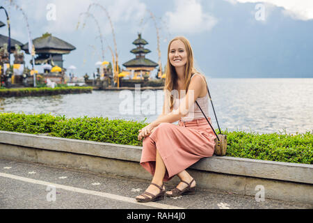 Young woman traveler in the background of Pura Ulun Danu Bratan, Bali. Hindu temple surrounded by flowers on Bratan lake, Bali. Major Shivaite water temple in Bali, Indonesia. Hindu temple - Stock Photo