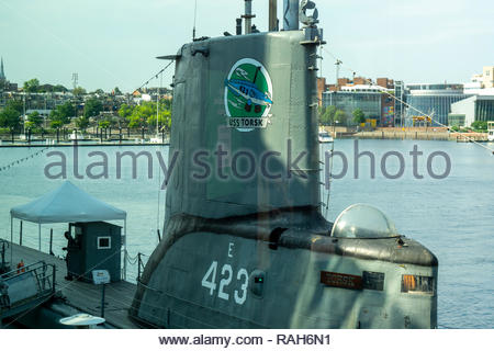 The USS Torsk, a US Navy submarine from World War II, is docked next to the National Aquarium at the Inner Harbor in Baltimore, Maryland USA - Stock Photo