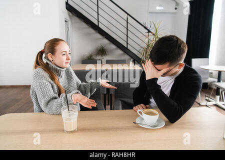 Bad relationship concept. Man and woman in disagreement. Young couple sitting in cafe having quarrel, offended wife and unhappy husband - Stock Photo