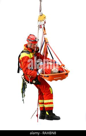 High-angle rescuer abseiling while rescuing a person in a rescue basket, a professional firefighter from the Berufsfeuerwehr - Stock Photo