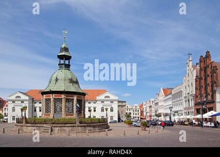Market square or market place with the Wasserkunst fountain and the 'Old Swede' warehouse, Wismar, Mecklenburg-Western Pomerania - Stock Photo