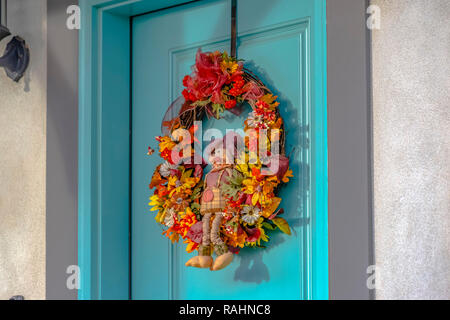 Colorful autumn wreath with small scarecrow on front door. The front door is blue and the wreath has leaves and flowers that are orange, red, yellow a - Stock Photo