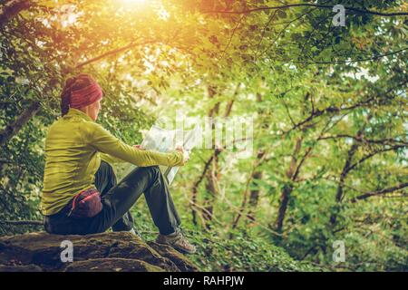 Female Hiker with Local Map in Hands Looking For the Next Destination. Travel and Recreation Theme. - Stock Photo
