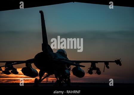 An F-16 Fighting Falcons sits on the flightline at sunset at the 407th Air Expeditionary Group Feb. 4, 2017. The F-16 is part of the 134th Expeditionary Fighter Squadron, supporting Operation Inherent Resolve in the fight against the Islamic State of Iraq and the Levant. - Stock Photo