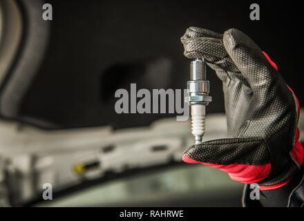 Automotive Industry. Vehicle Spark Plug in Car Mechanic Hand. - Stock Photo