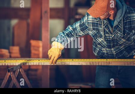 Caucasian Worker in His 30s Measure Wood Beam with Measuring Tape. - Stock Photo