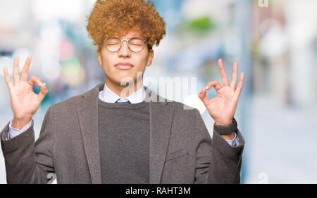 Young handsome business man with afro wearing glasses relax and smiling with eyes closed doing meditation gesture with fingers. Yoga concept. - Stock Photo