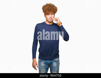 Young handsome man with afro hair mouth and lips shut as zip with fingers. Secret and silent, taboo talking - Stock Photo