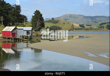 One of the many lagoons on the Otago peninsula reflecting charming boat houses on a sunny Summer day. - Stock Photo
