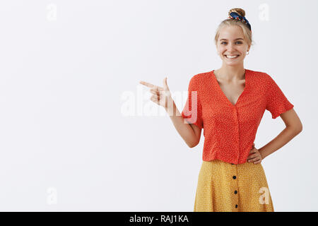 Studio shot of happy emotive young female designer in trendy vintage red blouse and mustard skirt, holding hand on waist and pointing left, showing great place for shopping and fun, smiling broadly - Stock Photo