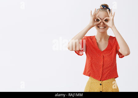 Inner kid wants play. Childish and playful good-looking happy blond female friend in vintage stylish red blouse and skirt, showing zero or okay gesture over eyes as if gazing through binocular or mask - Stock Photo