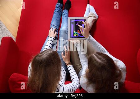 Two girls playing at home with an iPad, tablet computer, wireless internet access - Stock Photo