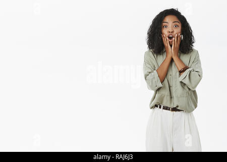 Portrait of emotive impressed dark-skinned female employee reacting on awesome surprising news touching face and opening mouth from amazement and happiness posing against gray background - Stock Photo