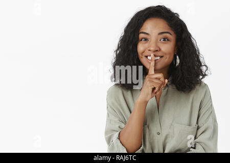 Shh can you keep secrets. Portrait of charming friendly-looking delighted cute dark-skinned woman with curly hairstyle saying shush and smiling preparing surprise posing mystrious over grey wall - Stock Photo