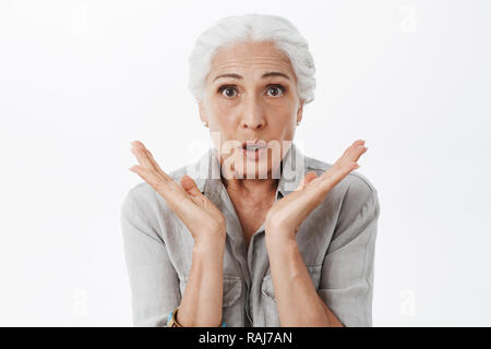 Waist-up shot of anxious and surprised kind grandmother feeling worried and amazed holding palms near face looking concerned and interested what happening against gray background - Stock Photo