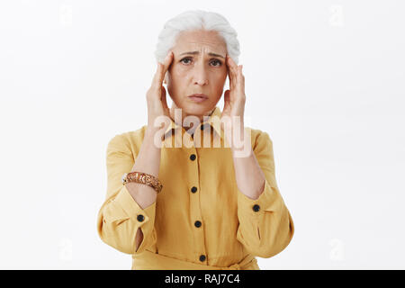 Studio shot of gloomy drained and upset old woman in trendy yellow coat holding hands on temples frowning from pain feeling migraine, suffering headache posing over white background - Stock Photo