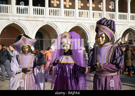 Venice, Italy - February 10, 2018: People in gold masks and purple costumes on the St Mark's Square (Piazza San Marco) at the Venice Carnival - Stock Photo