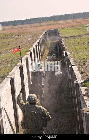 Soldiers from 1st Battalion, 64th Armor Regiment clear a trench during a company Combined Arms Live-Fire Exercise at Fort Stewart, Georgia Feb. 4 2017. - Stock Photo