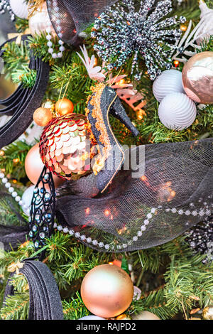 Lady's high-heeled shoe hangs on a Christmas tree decorated with toys and garlands, balls and snowflakes, beads and glowing bulbs - Stock Photo