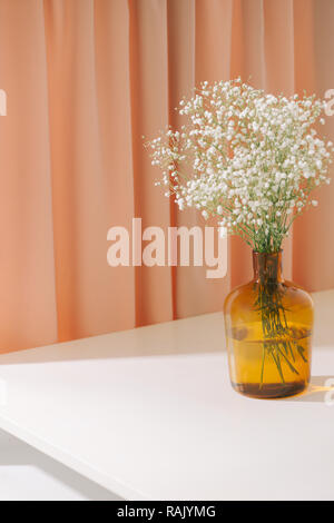 Gypsophila (Baby's breath flowers), in glass bottle on textured background. Beautiful light, airy masses of small white flowers. floral still life as  - Stock Photo