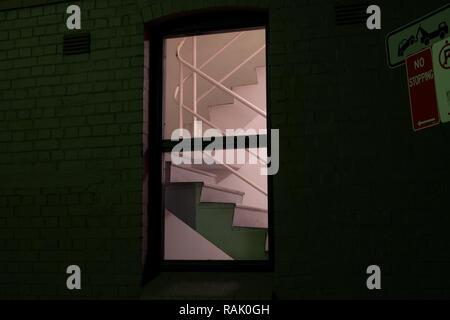 eerie scene of stairwell seen through a window - Stock Photo