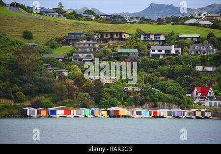 Brightly colored boat houses along the shore of the Banks peninsula near Christchurch and Akaroa on the South island of New Zealand. - Stock Photo