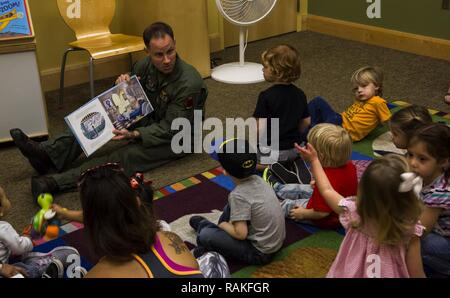 U.S. Marine Corps Maj. Benjamin D. Apple, the operations officer for Marine Fighter Training Squadron 401 (VMFT-401), stationed out of Marine Corps Air Station Yuma, Ariz., reads 'Violet Pilot,' an aviation-themed children's book to families at the main Yuma County Library, Wednesday, Feb. 15, 2017. - Stock Photo