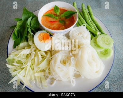 Thai rice noodle or rice vermicelli noodle and curry soup sauce on plate with vegetable yardlong , cucumber  bean and egg / Thai style food delicious - Stock Photo