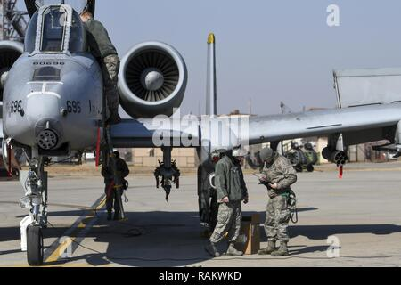 Airmen assigned to the 25th Aircraft Maintenance Unit perform pre-flight checks on an A-10 Thunderbolt II assigned to the 25th Fighter Squadron during Buddy Wing 17-3 at Osan Air Base, Republic of Korea, Feb. 14, 2017. During Buddy Wing 17-3, pilots from the 25th FS and the ROK air force 237th Tactical Control Squadron flew training missions to increase to the two units' ability to work together in a wartime scenario. - Stock Photo