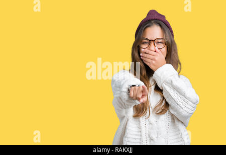 Young beautiful brunette hipster woman wearing glasses and winter hat over isolated background Laughing of you, pointing to the camera with finger han - Stock Photo