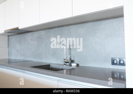 Modern kitchen with metal faucet,  ceramic kitchen sink, kitchen stove, kitchen hood - Stock Photo