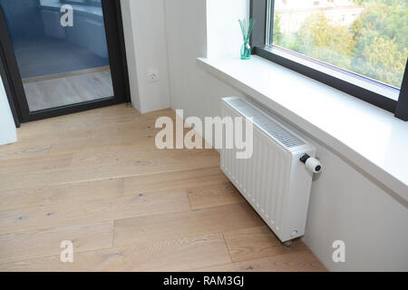 White radiator heating with thermostat for energy saving in unfinished home room repair with balcony door. - Stock Photo