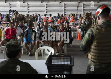 Military and civilian role players from the Thailand, Malaysia,  Japan and the U.S. sit in a holding area during a noncombatant  evacuation operation exercise during Cobra Gold  2017 at Utapao International Airport in Rayong Province,  Thailand, Feb. 19, 2017. Cobra Gold, in its 36th iteration,  focuses on humanitarian civic action, community  engagement, and medical activities to support the needs  and humanitarian interest of civilian populations around the  region. - Stock Photo