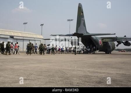 Japanese Self-Defense Force (JSDF) service members escort Japanese citizens onto a JSDF C-130 aircraft during a noncombatant evacuation operation exercise during Cobra Gold 2017 at Utapao International Airport in Rayong Province, Thailand, Feb. 19, 2017. Cobra Gold, in its 36th iteration, focuses on humanitarian civic action, community engagement,  and medical activities to support the needs and humanitarian interest of civilian populations around the region. - Stock Photo
