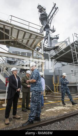 A U.S. Sailor speaks with D'Arcy Neller, wife of Commandant of the Marine Corps Gen. Robert B. Neller, Pascagoula, Miss., Feb. 21, 2017. Neller received a tour of the USS John Finn DDG 113 after the keel laying ceremony for Frank E. Petersen, Jr. DDG 121. - Stock Photo