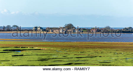 The isolated houses on Sunderland Point, Lancashire,  which is cut off at high tide. Photo taken from across the River Lune at Glasson Dock - Stock Photo