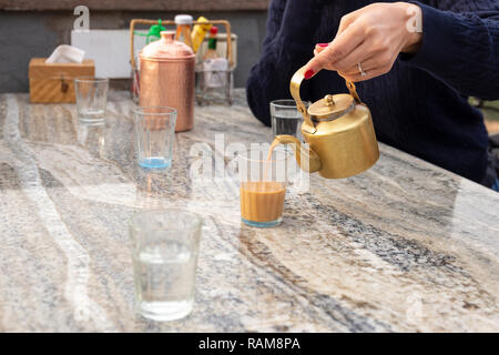 Woman pouring masala tea from teapot into cupglass on table in cafe. - Stock Photo