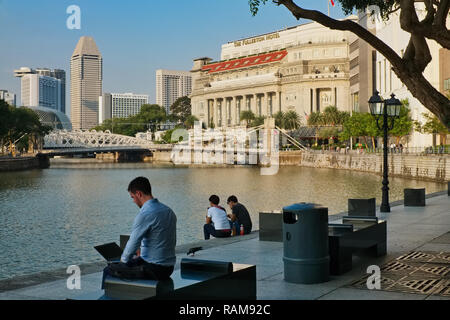 People relaxing by the Singapore River near Boat Quay, in the background Cavenagh Bridge and Fullerton Hotel (right) - Stock Photo