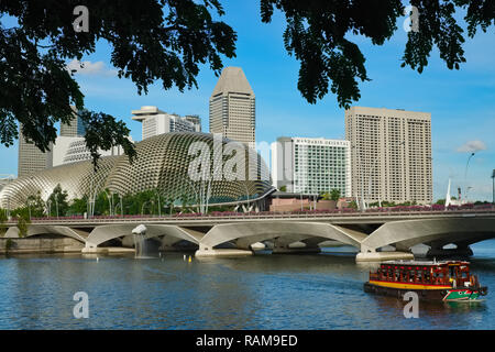 An excursion boat on the Singapore River, with Theatres on The Bay (l) and office and hotel towers near Marina Bay in the background; Singapore - Stock Photo